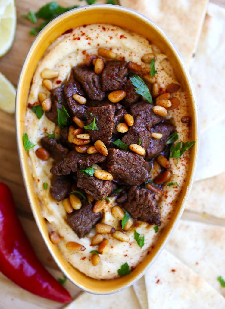 Hummus with grilled beef and pine nuts.