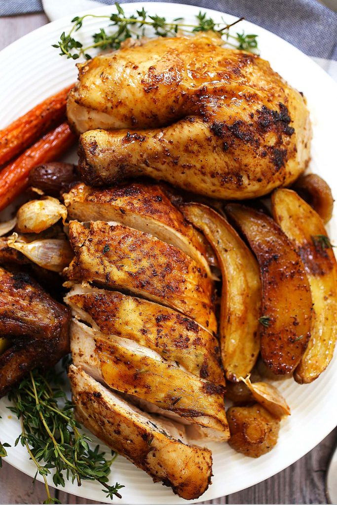 Roasted chicken with vegetables on a plate.