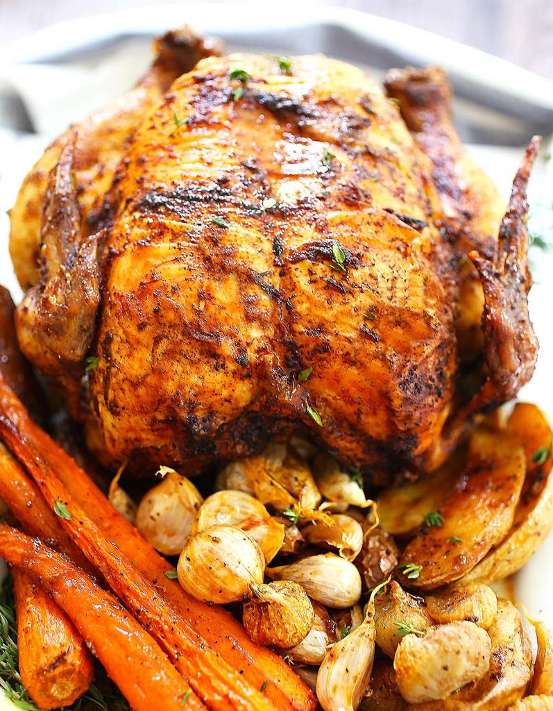 Whole roasted chicken with garlic and vegetables.