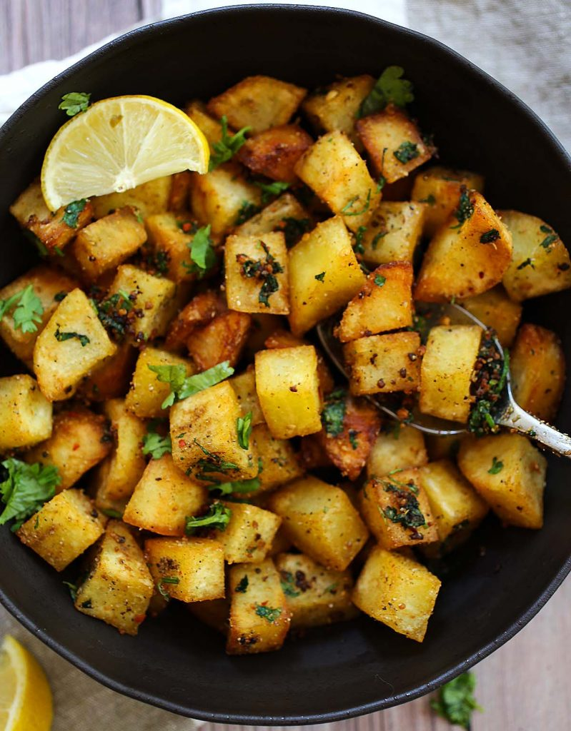 Spiced potatoes with lemon wedge.