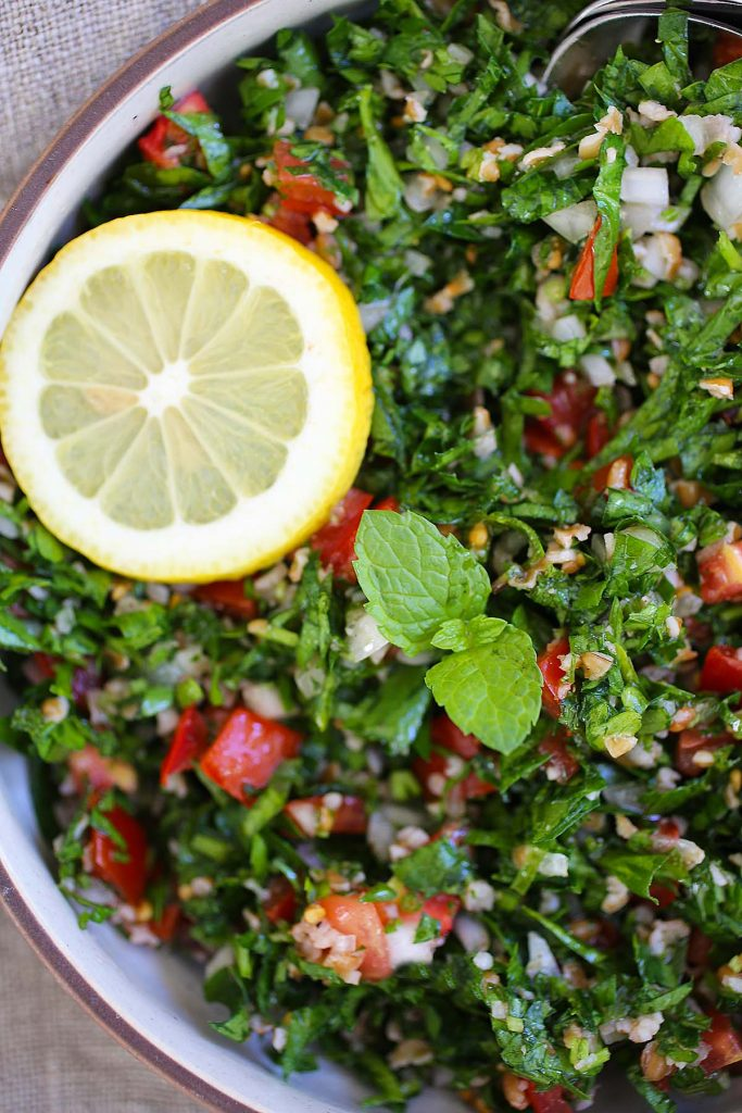 Tabbouleh salad with lemon wedge.