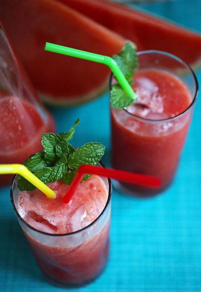 Fresh watermelons and juice in glass cups.