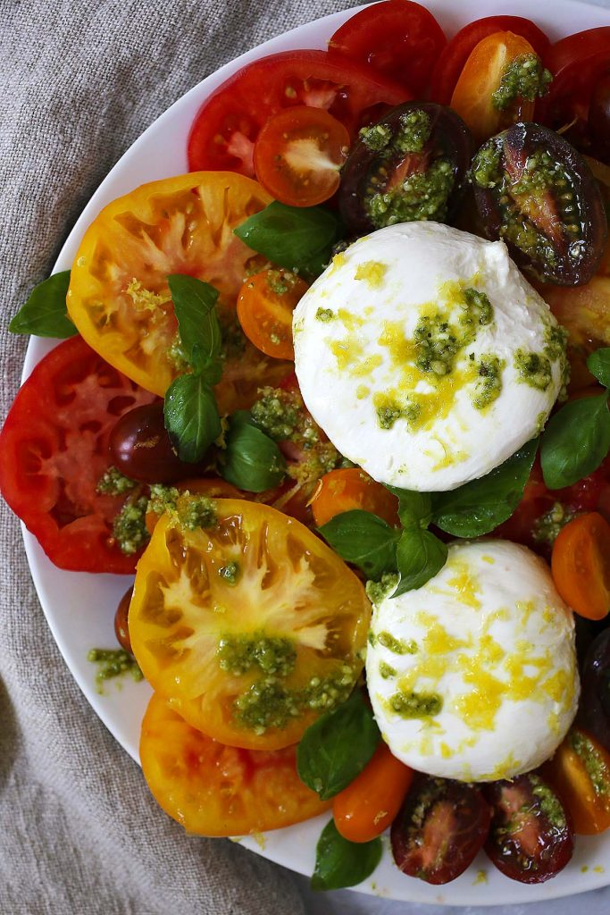 Colorful tomatoes with pesto and cheese on plate.
