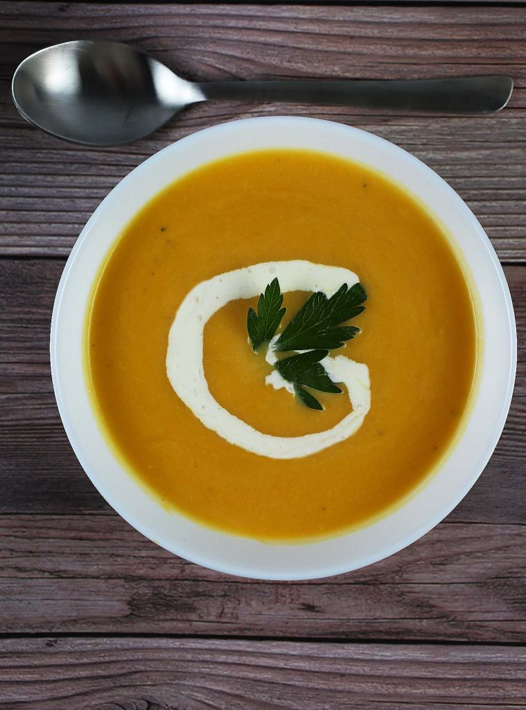 Butternut soup with cream in bowl.