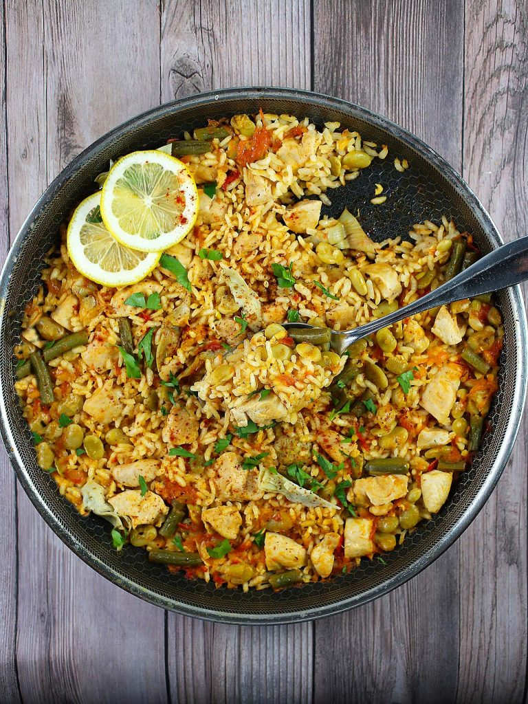 Valencian paella with chicken and lemon slices in pan.