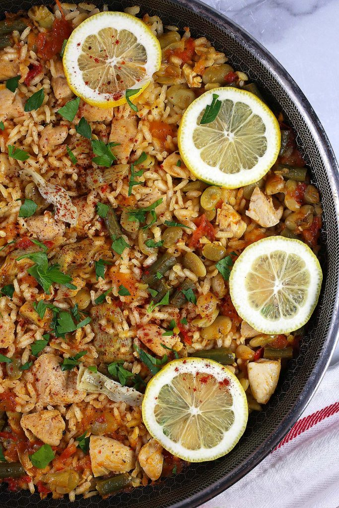 Paella with chicken and lemon slices.