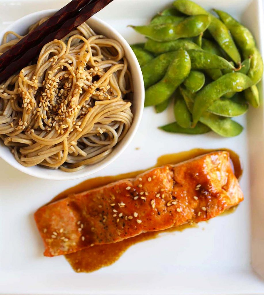 Salmon with soba noodles and edamame on a plate.