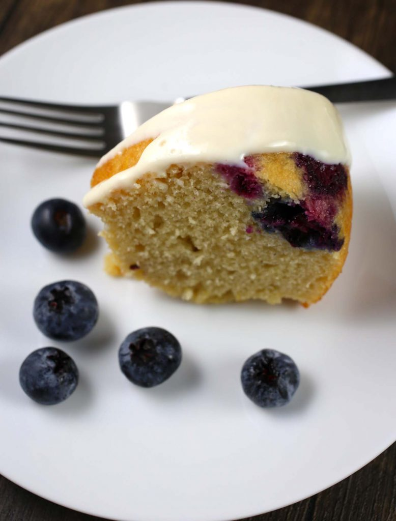 Slice of cake with cream cheese frosting and blueberries.
