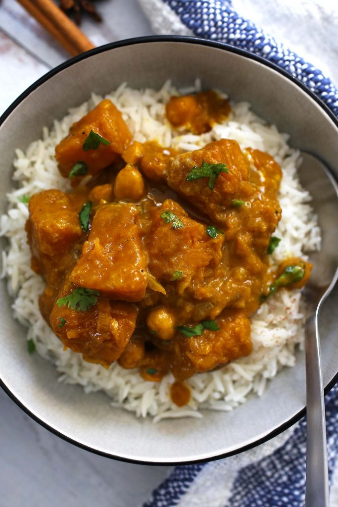 Pumpkin spice curry with chickpeas and coconut cream with white rice in plate.
