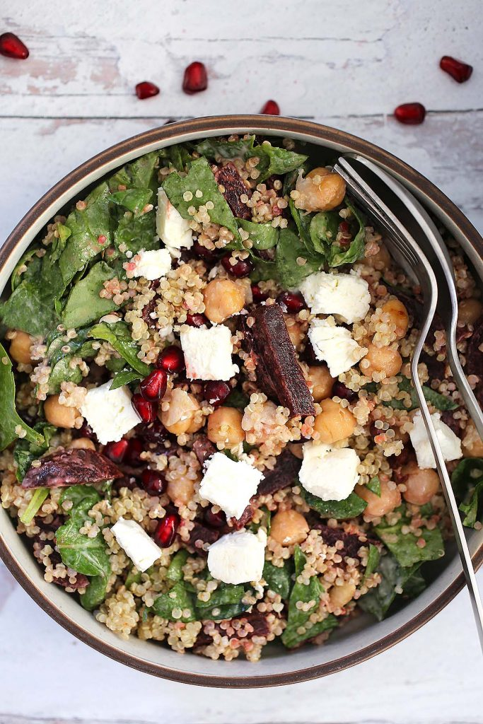 Quinoa spinach salad with chickpeas, beets, feta cheese and tahini sauce.