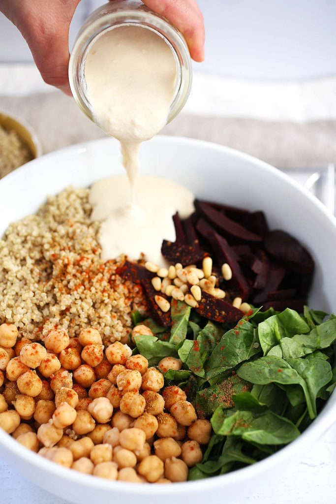 Quinoa spinach salad with chickpeas, beets, feta cheese and adding tahini sauce from jar.