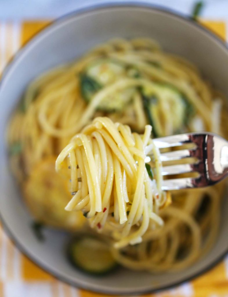 spaghetti with zucchini on fork.