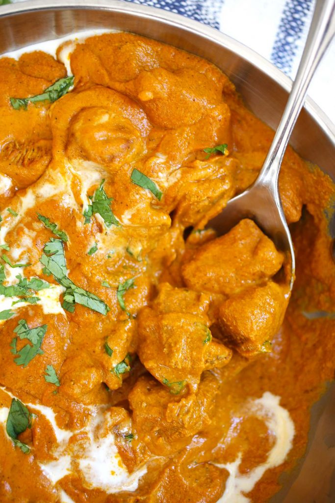 A spoonful of  Butter chicken.