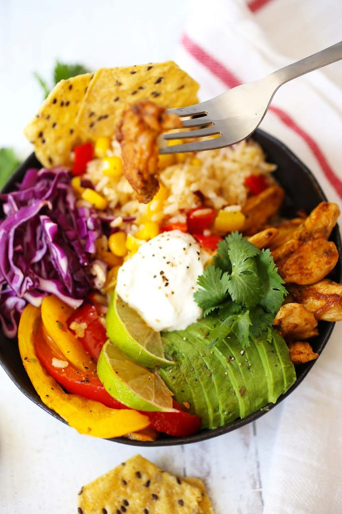 Chicken fajita rice bowl with sour cream, avocado, lime and cilantro.