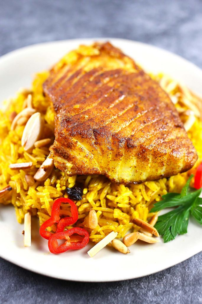 Basmati rice with spiced fish on plate.