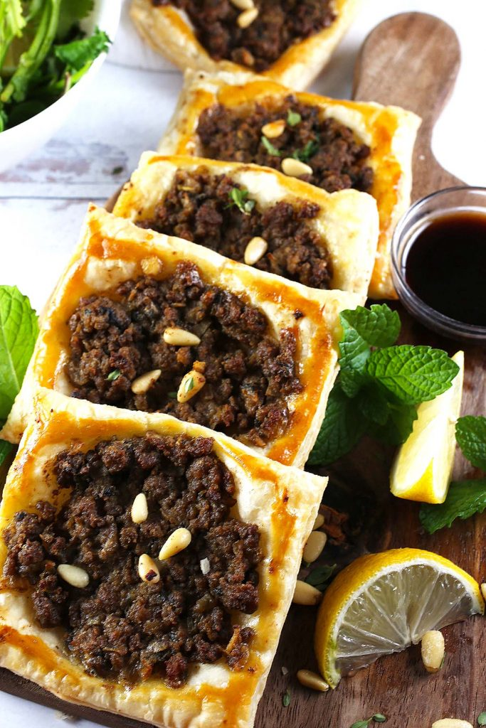 Puffs filled with spiced beef on wooden tray.