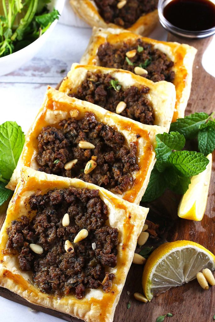 Beef puffs with lemon wedges and fresh mint.