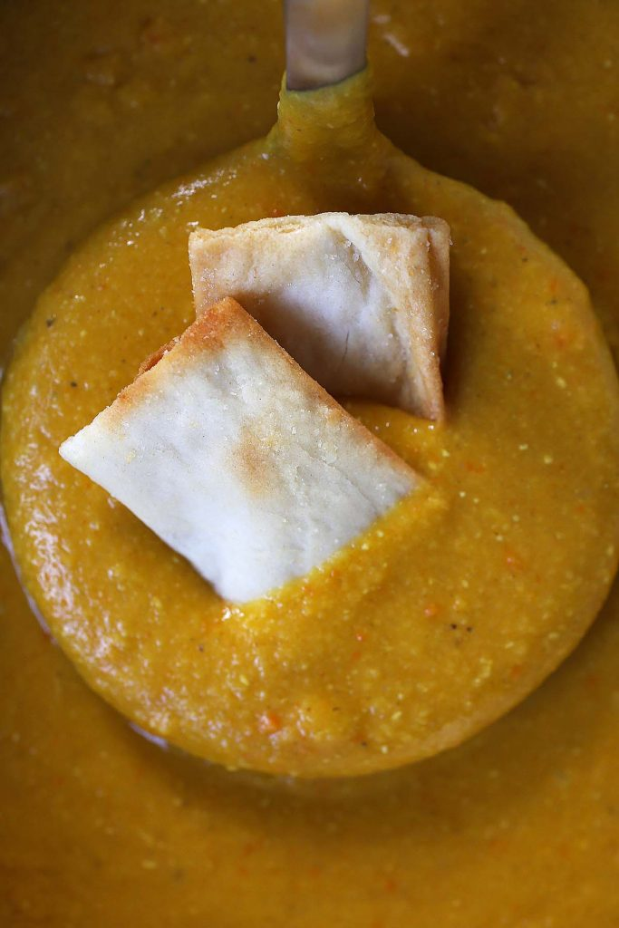 Lentil Soup in ladle with 2 pita chips.