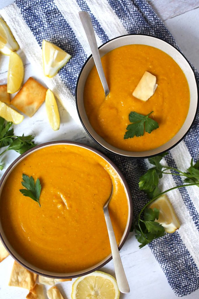 Lentil Soup in plates with lemon wedges and parsley