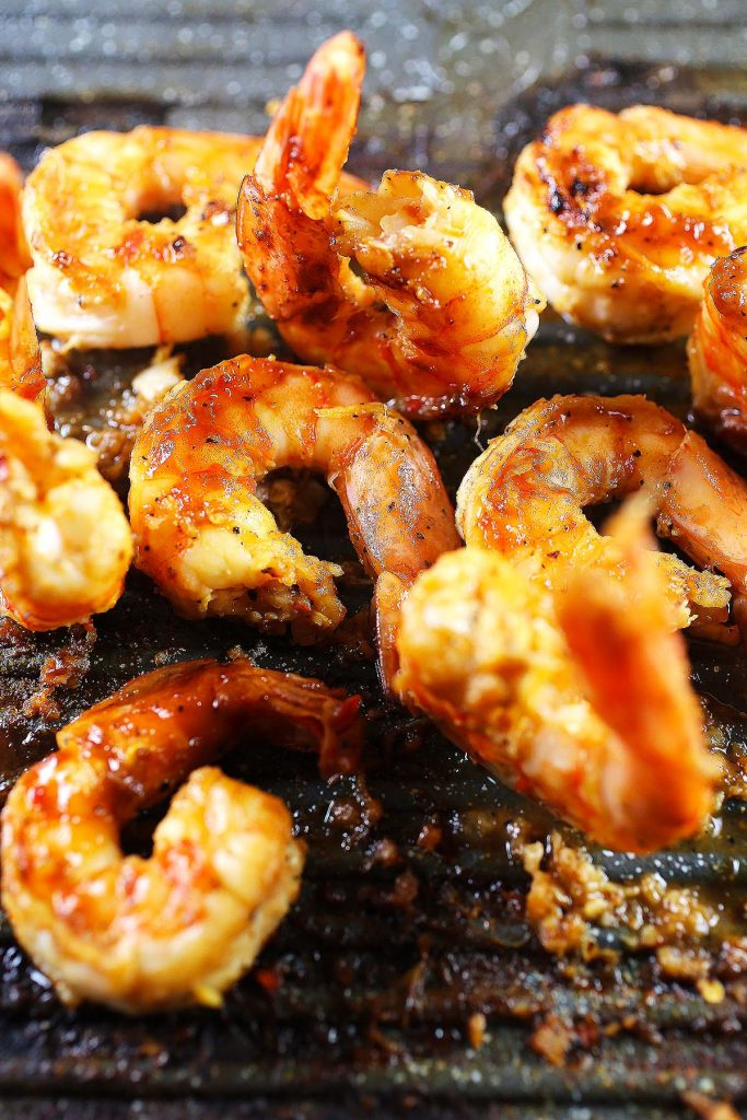 Spicy honey grilled shrimp on grill.