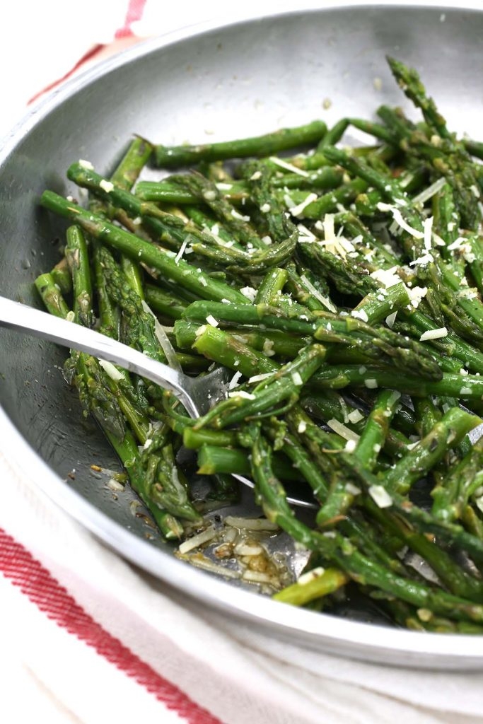 Sauteed asparagus in pan with Parmesan cheese.