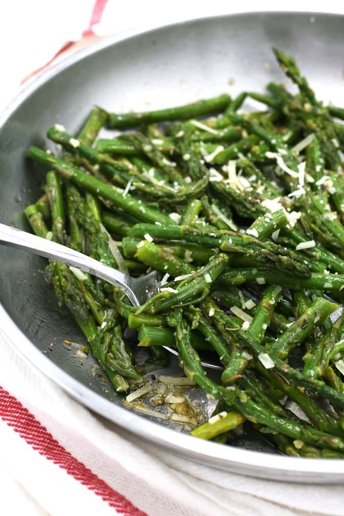 Asparagus with garlic and cheese in pan.