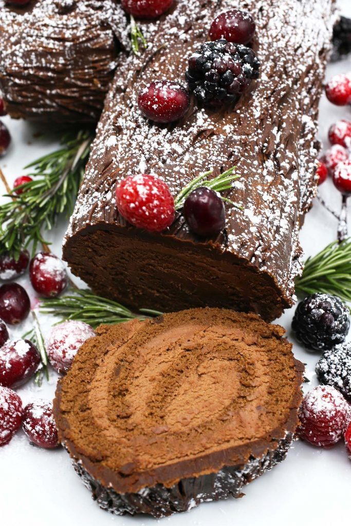 Yule log with chocolate cheese filling and berries on top.