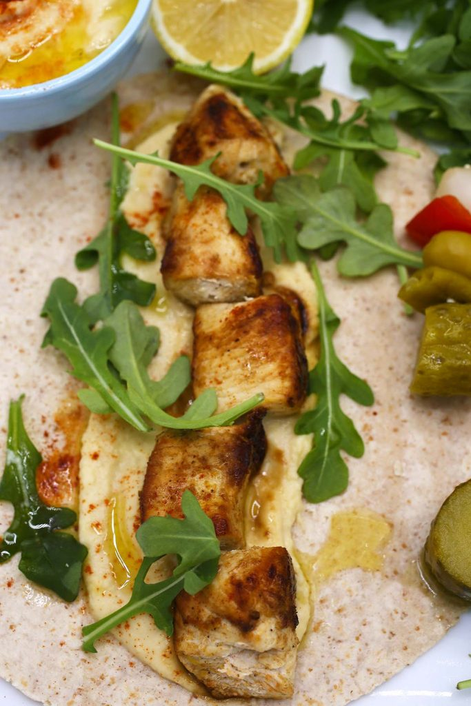 Chicken and hummus wrap with arugula.