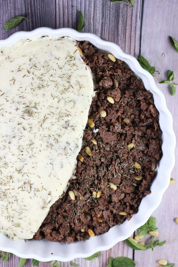 Pan cooked beef with pine nuts in baking dish.