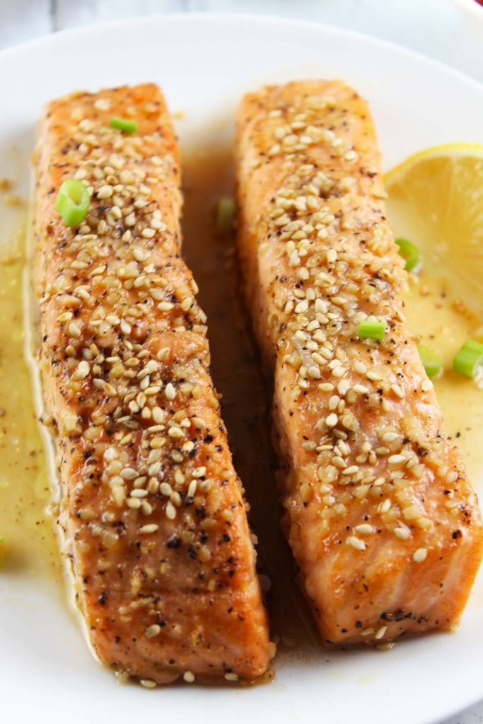 Salmon in sauce with sesame seeds on top.