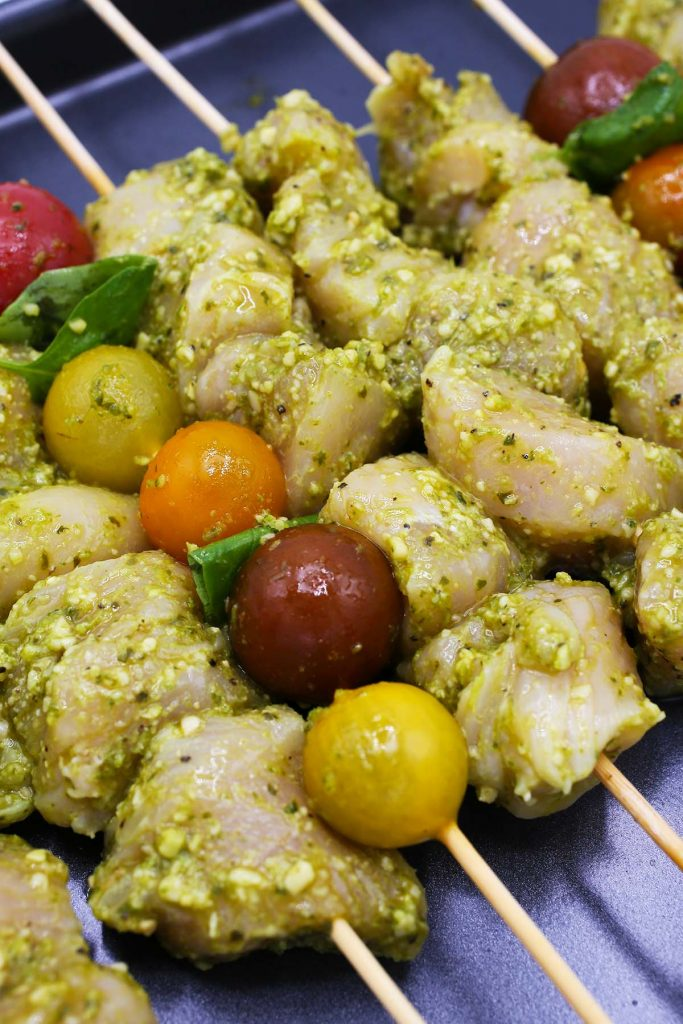 Raw chicken kebabs marinated in pesto.