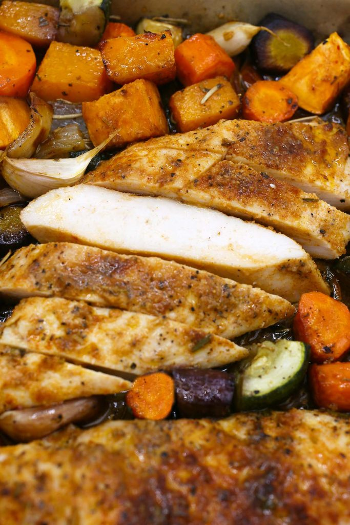 Grilled chicken breast cut to pieces with vegetables on the side.