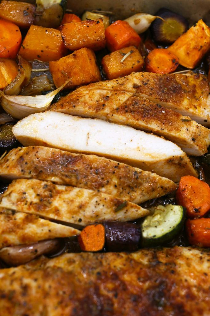 Cut up chicken breast with baked vegetables.