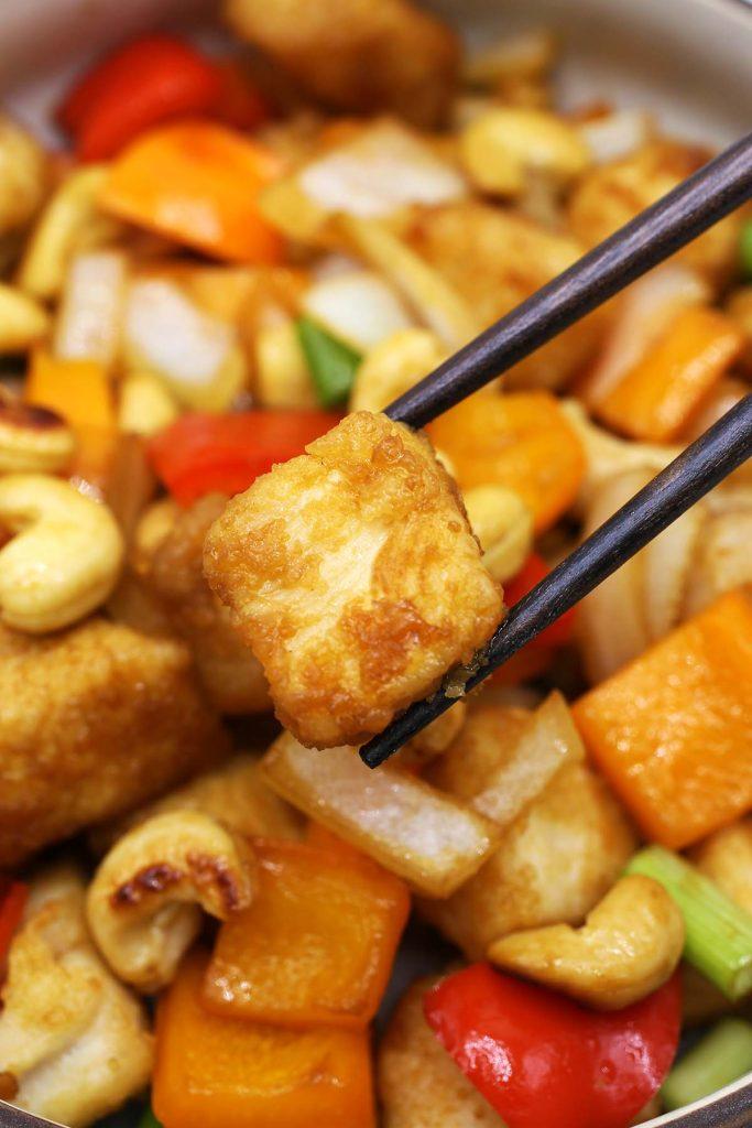 Chicken piece in chopsticks.
